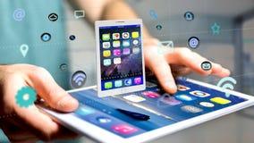 Homem de negócios que usa um smartphone com uma tabuleta que cerca pelo app Fotografia de Stock Royalty Free