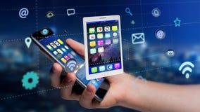 Homem de negócios que usa um smartphone com uma tabuleta que cerca pelo app Imagem de Stock