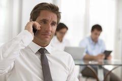 Homem de negócios que usa um smartphone durante uma reunião Fotos de Stock Royalty Free