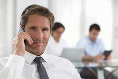 Homem de negócios que usa um smartphone durante uma reunião Fotos de Stock