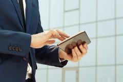 Homem de negócios que usa uma tabuleta digital fora Fotografia de Stock