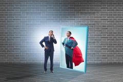 Homem de negócios que vê-se no espelho como o super-herói fotografia de stock