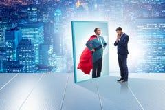 Homem de negócios que vê-se no espelho como o super-herói imagens de stock