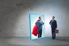 Homem de negócios que vê-se no espelho como o super-herói foto de stock