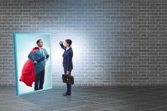 Homem de negócios que vê-se no espelho como o super-herói imagens de stock royalty free
