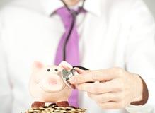 Homem de negócios que verific o banco piggy Imagens de Stock