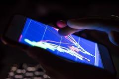 Homem de negócios que verifica as cartas conservadas em estoque em um dispositivo móvel imagem de stock royalty free