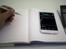 Homem de negócios que verifica dados do mercado de valores de ação foto de stock