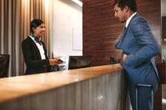 Homem de negócios que verifica dentro na recepção do hotel fotografia de stock royalty free