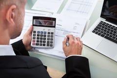 Homem de negócios que verifica figuras em um relatório Imagens de Stock Royalty Free
