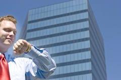 Homem de negócios que verifica o tempo fotografia de stock