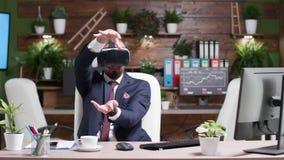 Homem de negócios que veste uns auriculares aumentados da realidade video estoque