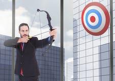 Homem de negócios que visa a placa do alvo contra prédios de escritórios no fundo Fotografia de Stock Royalty Free