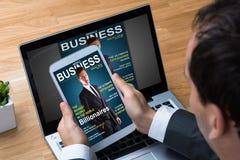 Homem de negócios Reading Business Magazine na tabuleta fotografia de stock