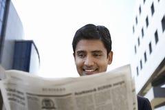 Homem de negócios Reading Newspaper Outdoors imagens de stock royalty free