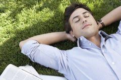Homem de negócios relaxado Lying On Grass no parque Imagens de Stock Royalty Free