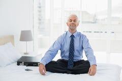 Homem de negócios relaxado que senta-se com os olhos fechados na cama imagem de stock royalty free