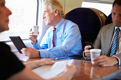 Homem de negócios Relaxing On Train com xícara de café Fotografia de Stock Royalty Free