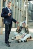 Homem de negócios rico de Lderly que dá algum dinheiro ao pobre homem imagens de stock