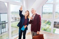 Homem de negócios rico que pensa sobre a compra da casa nova que está o agente imobiliário próximo fotos de stock