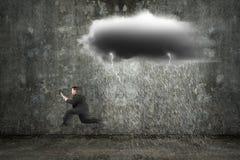 Homem de negócios running que guarda a tabuleta com as nuvens escuras que chovem e Foto de Stock