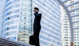Homem de negócios sério com fala do smartphone Fotografia de Stock Royalty Free