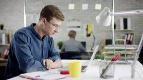 Homem de negócios sério concentrado produtivo que inclina o trabalho de escritório para trás de terminação no portátil, gerente e filme