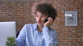 Homem de negócios sério do lerdo que fala no telefone e que trabalha no portátil, sentando-se na tabela no escritório moderno com vídeos de arquivo