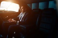 Homem de negócios sério em um carro com portátil foto de stock