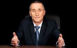 Homem de negócios sério no escritório com mãos abertas Fotografia de Stock