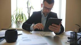 Homem de negócios sério nos monóculos que olham diagramas com estatísticas em papéis ao trabalhar no dispositivo digital video estoque