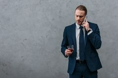 homem de negócios sério novo com vidro da fala do uísque imagens de stock royalty free