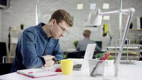Homem de negócios sério produtivo que inclina o trabalho de escritório para trás de terminação no portátil, gerente eficaz satisf filme