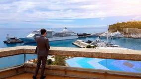 Homem de negócios sério que fala no telefone, apreciando a vista do iate novo, porto privado foto de stock royalty free