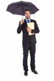 Homem de negócios sério que guarda um arquivo sob o guarda-chuva Foto de Stock Royalty Free