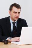 Homem de negócios sério que trabalha no lap-top Fotos de Stock