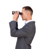 Homem de negócios sério que usa binóculos Fotografia de Stock Royalty Free