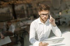 Homem de negócios sério que usa o telefone celular e a tabuleta fotografia de stock