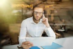 Homem de negócios sério que usa o telefone celular e a tabuleta imagens de stock