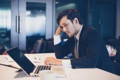 Homem de negócios sério sobre o trabalho feito duramente até a dor de cabeça fotografia de stock royalty free
