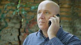 Homem de negócios sério Talking à parte externa do telefone celular imagem de stock