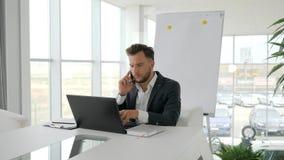 Homem de negócios sério Works no portátil no Internet na sala de reuniões, conversa do executivo empresarial no móbil no local de vídeos de arquivo