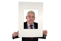Homem de negócios sênior com a montagem da foto que faz as faces Foto de Stock Royalty Free