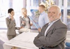 Homem de negócios sênior de sorriso orgulhoso com equipe imagens de stock royalty free