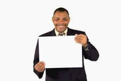 Homem de negócios sênior de sorriso que apresenta uma placa Fotografia de Stock Royalty Free