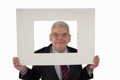 Homem de negócios sênior de sorriso que prende uma montagem da foto Fotografia de Stock