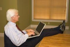 Homem de negócios sênior no portátil imagens de stock royalty free