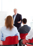 Homem de negócios sênior que dá uma conferência