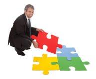 Homem de negócios sênior que monta um enigma de serra de vaivém imagens de stock royalty free
