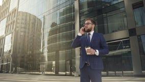 Homem de negócios seguro com café à disposição, falando no telefone na rua da metrópole video estoque
